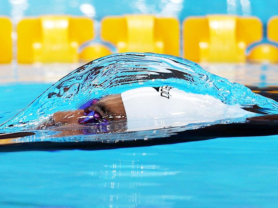 A water bubble forms around a swimmer coming to the surface at the Tokyo Olympics.