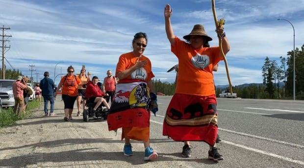 Lorraine Netro, centre left, and Jacqueline Shorty, right, walk down the Klondike Highway in Whitehorse. They plan to be in Kamloops B.C. by August 9. (Chris MacIntyre/CBC - image credit)