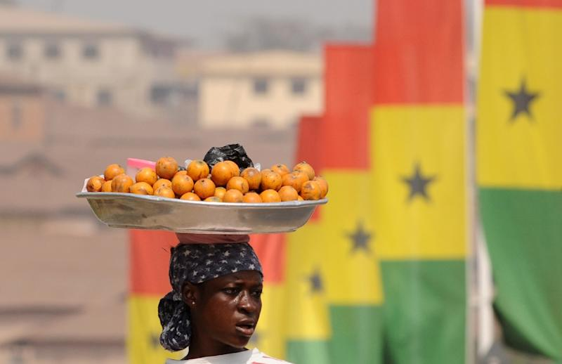 A local vendor offers her goods in Kumasi, Ghana which has cut its poverty rate from 53 percent in 1991 to 21 percent in 2012 (AFP Photo/Joe Klamar)