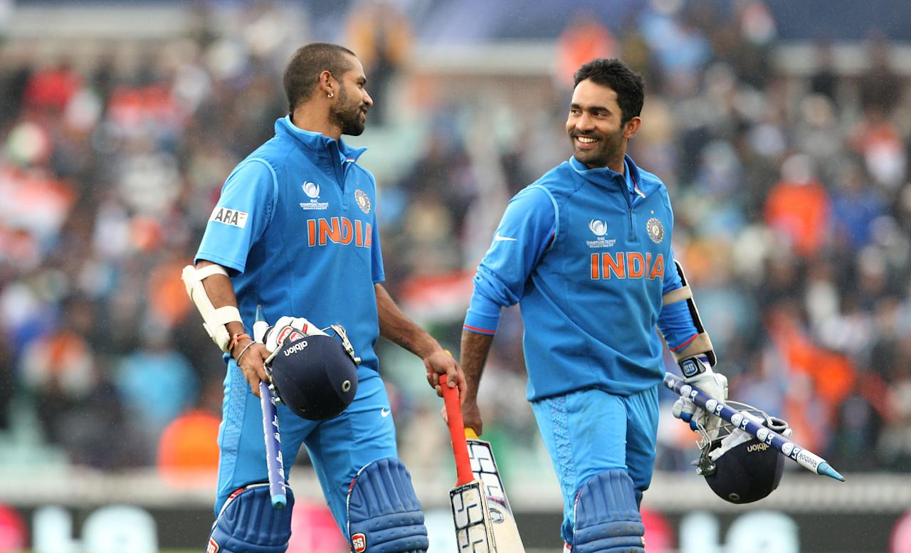 India batsmen Shikhar Dhawan (left) and Dinesh Karthik leave the field after victory against West Indies during the ICC Champions Trophy match at the Kia Oval, London.