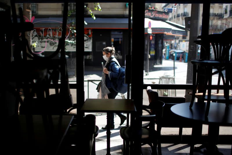 FILE PHOTO: A woman wearing a protective face mask walks past a closed restaurant in Paris
