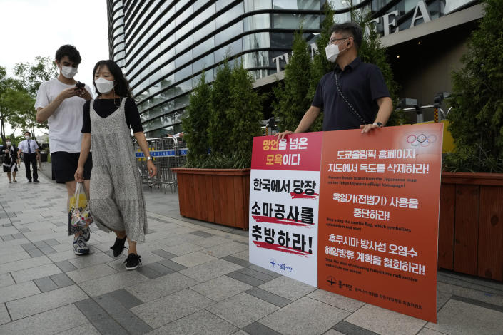"""A protester stands to oppose South Korean President Moon Jae-in's possible visit to Japan in front of a building which houses Japanese embassy in Seoul, South Korea, Monday, July 19, 2021. Moon has decided not to visit Japan for the Tokyo Summer Olympics, citing a failure to set up a summit with Japan's prime minister that would produce meaningful results in improving relations. The signs on a banner at left read """"Expel Hirohisa Soma, deputy chief of mission at the Japanese Embassy in Seoul, from South Korea."""" (AP Photo/Ahn Young-joon)"""
