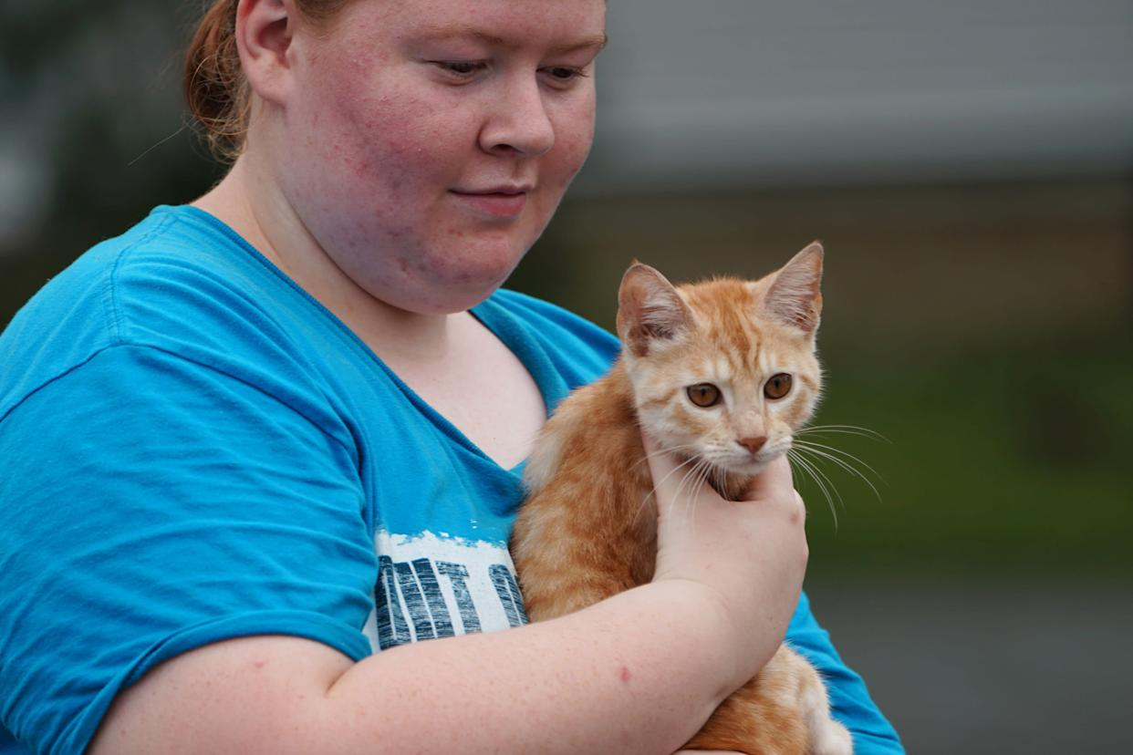A woman carries her cat on a flooded street after Hurricane Florence struck Piney Green, North Carolina, U.S., September 16, 2018.