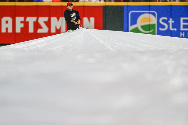 A member of the grounds crew helps pull a tarp over the infield during a rain delay in the fourth inning baseball game between the Cincinnati Reds and the Pittsburgh Pirates, Saturday, July 21, 2018, in Cincinnati. (AP Photo/John Minchillo)