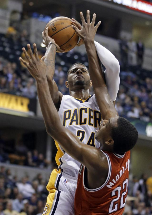 Indiana Pacers forward Paul George, top, shoots over Milwaukee Bucks forward Khris Middleton in the second half of an NBA basketball game in Indianapolis, Friday, Nov. 15, 2013. The Pacers defeated the Bucks 104-77. (AP Photo/Michael Conroy)