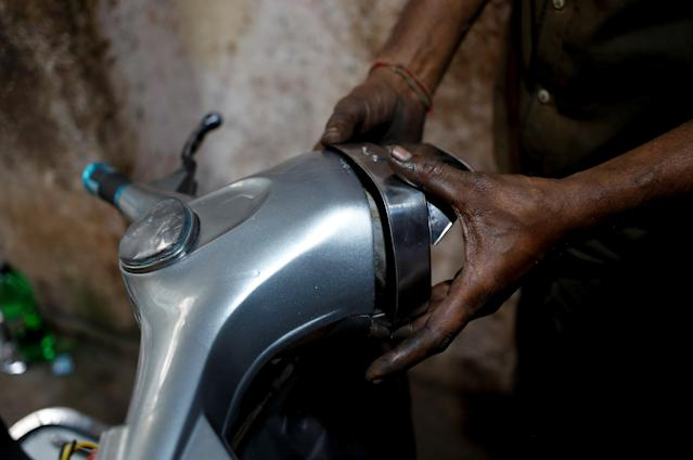 <p>A mechanic puts a headlight on a Vespa scooter, after repairing it at a workshop in Karachi, Pakistan March 1, 2018. (Photo: Akhtar Soomro/Reuters) </p>