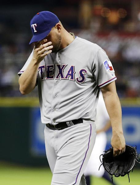 Texas Rangers pitcher Matt Harrison is replaced by Derek Lowe during the sixth inning of a baseball game against the Houston Astros, Sunday, March 31, 2013, in Houston. (AP Photo/Pat Sullivan)