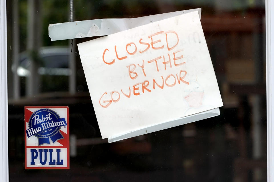 """A sign on the door of the West Alabama Icehouse reads """"Closed by the Governor"""", Monday, June 29, 2020, in Houston. Texas Gov. Greg Abbott shut down bars again and scaled back restaurant dining on Friday as cases climbed to record levels after the state embarked on one of America's fastest reopening. (AP Photo/David J. Phillip)"""