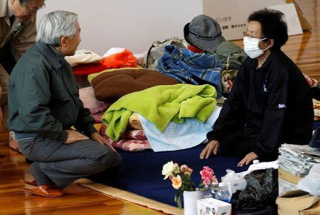 FILE PHOTO: Japan's Emperor Akihito (R) talks to an evacuee at a relocation center for people who fled their houses because of radiation fear by the March 11 tsunami-damaged Fukushima Daiichi Nuclear Power Plant in Fukushima, northeastern Japan, May 11, 2011, two months after the massive earthquake and tsunami. REUTERS/Shizuo Kambayashi/Pool/File Photo
