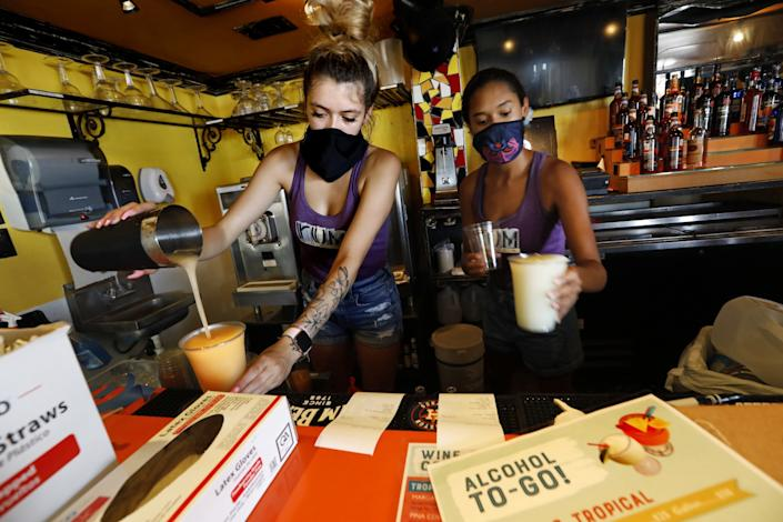 Nila White, left, and Brooklin Lafong make cocktails to go at The Spot, a restaurant and bar in Galveston, Texas.