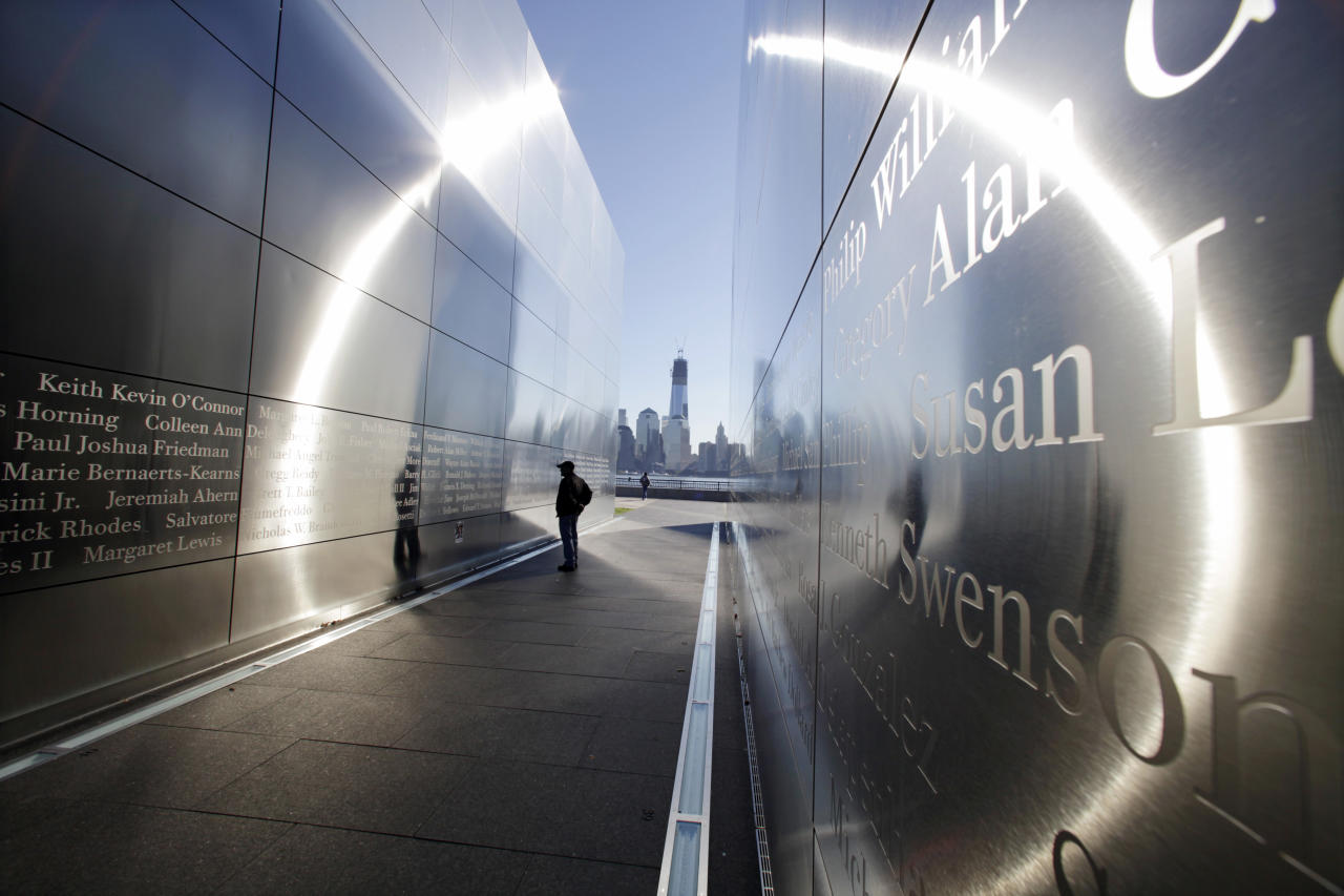A person stops to read names in New Jersey's memorial to the 749 people from the state lost during the  Sept. 11 terrorist attacks on the World Trade Center, as One World Trade Center, now up to 104 floors, looms in the distance across the Hudson River, Tuesday, Sept. 11, 2012 in Jersey City, N.J. (AP Photo/Mel Evans)