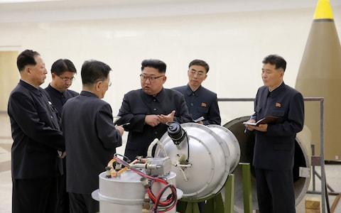 Kim Jong-un with regime engineers at an undisclosed location - Credit: Korea News Service via AP