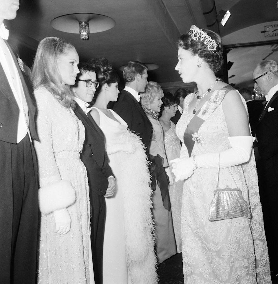 <p>Ursula Andress looked glamorous in a white sequin embroidered gown with fur trimmed sleeves while meeting Queen Elizabeth at a film premiere in London.</p>