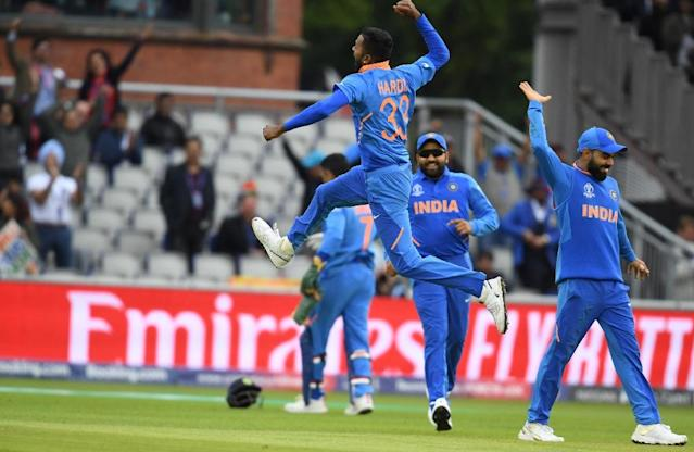 India's Hardik Pandya leaps into the air as he celebrates with teammates after the dismissal of Pakistan's Shoaib Malik (AFP Photo/Dibyangshu SARKAR)