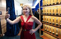 <p>Presenter Reese Witherspoon snaps a selfie in front of a wall of little gold men during the show. </p>