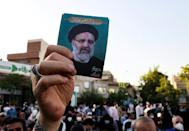 A supporter holds up a photograph of ultraconservative cleric Ebrahim Raisi, the favourite to win Friday's Iranian presidential election, at a rally in Tehran on the final day of the campaign