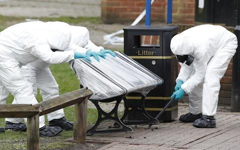 Police in protective suits and gas masks work to remove the bench where Sergei Skripal and his daughter Yulia were found poisoned - Credit: London News Pictures