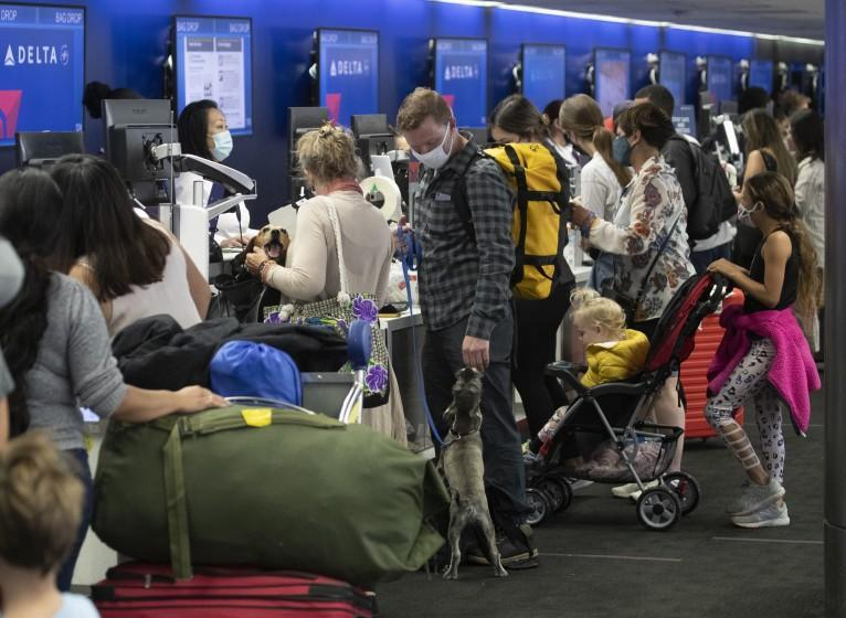 """Los Angeles, CA - May 28: Amid a busy getaway travel day for the Memorial Day weekend and the first holiday since coronavirus pandemic restrictions have been relaxed, a crowd of travelers check in for their flights at LAX at Delta Airlines, Terminal 2 at LAX Friday, May 28, 2021. Officials say travelers should arrive early for Memorial Day weekend flights. After months of Los Angeles International Airport looking like a ghost town, holiday crowds are back. """"We're seeing more travelers than we've seen in the last 14 months. We had over 75,000 people come through on Sunday alone to the TSA checkpoints, that's by far a record in 2021 for us,"""" said LAX spokesperson Keith Montgomery. Photo taken in LAX on Friday, May 28, 2021 in Los Angeles, CA. (Allen J. Schaben / Los Angeles Times)"""