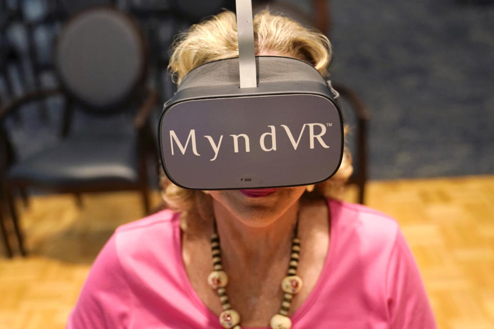 Resident Janet Anding wears goggles as she participates in a virtual reality study at John Knox Village, Tuesday, June 1, 2021, in Pompano Beach, Fla. The senior community is in partnership with Stanford University's Virtual Human Interaction Lab on a study to see how older adults respond to virtual reality and whether it can improve their sense of wellbeing. (AP Photo/Lynne Sladky)