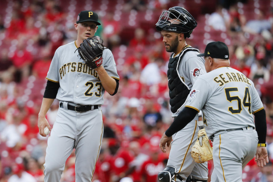 CORRECTS CITY TO CINCINNATI NOT COLUMBUS - Pittsburgh Pirates starting pitcher Mitch Keller (23) meets with catcher Jacob Stallings, center, and pitching coach Ray Searage (54) after giving up a grand slam to Cincinnati Reds' Jose Iglesias in the first inning during the second baseball game of a doubleheader, Monday, May 27, 2019, in Cincinnati. (AP Photo/John Minchillo)