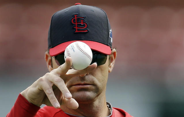 St. Louis Cardinals manager Mike Matheny balances a baseball between his fingers as he prepares to throw batting practice Thursday, Oct. 10, 2013, in St. Louis. The Cardinals are scheduled to play the Los Angeles Dodgers in Game 1 of baseball's National League championship series on Friday in St. Louis. (AP Photo/Jeff Roberson)