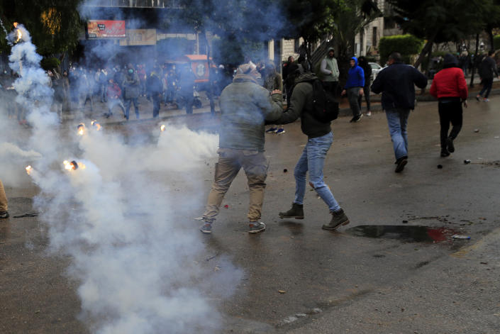 Protesters run from tear gas canisters during a protest against deteriorating living conditions and strict coronavirus lockdown measures, in Tripoli, north Lebanon, Thursday, Jan. 28, 2021. Violent confrontations for three straight days between protesters and security forces in northern Lebanon left a 30-year-old man dead and more than 220 people injured, the state news agency said Thursday. (AP Photo/Hussein Malla)