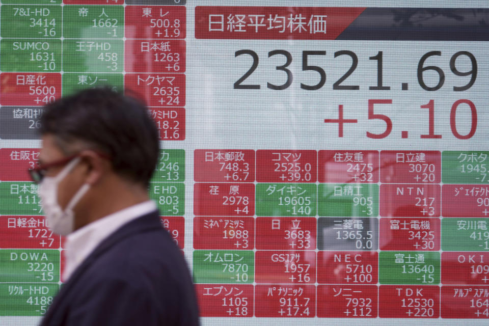 A man walks past an electronic stock board showing Japan's Nikkei 225 index at a securities firm in Tokyo Monday, Oct. 26, 2020. Asian shares were little changed in muted trading Monday amid widespread uncertainty over what the U.S. presidential election will portend for markets and economic policy.(AP Photo/Eugene Hoshiko)