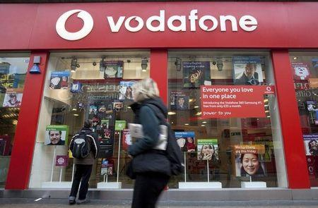 A pedestrian passes a Vodafone store on Oxford Street in central London