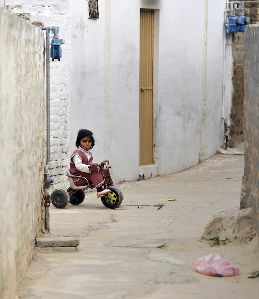 A young girl plays outside the family residence of former Pakistani cricketer Mohmammad Aamer in Changa Bangial village some 73 kilometres east of Islamabad on Febraury 2, 2012. Disgraced Pakistan cricketer Mohammad Aamer will announce his next move when he returns home later this month after his release from a British prison, his brother told AFP. Aamer was one of three Pakistan players jailed by a judge in London in November over their roles in a plan to bowl deliberate no-balls during a Test against England at Lord's in August 2010. (AAMIR QURESHI/AFP/Getty Images)