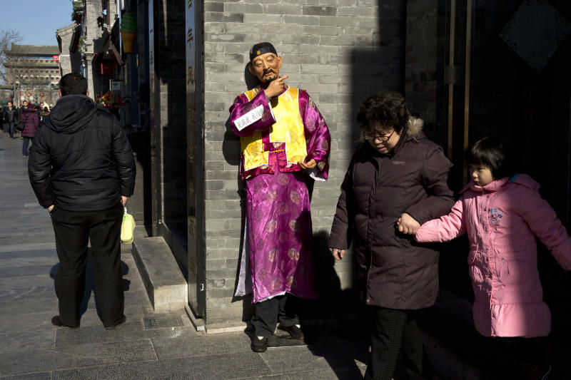 A woman walks with her granddaughter by a shop with an advertising mascot while a man, left, waits for customers at the entrance to a restaurant on a shopping street in Beijing Thursday, Jan. 30, 2014. The reluctance of customers to open their wallets wider is one of a thicket of obstacles facing communist leaders as they try to rebalance China's economy away from reliance on investment that is losing its ability to boost growth. (AP Photo/Alexander F. Yuan)