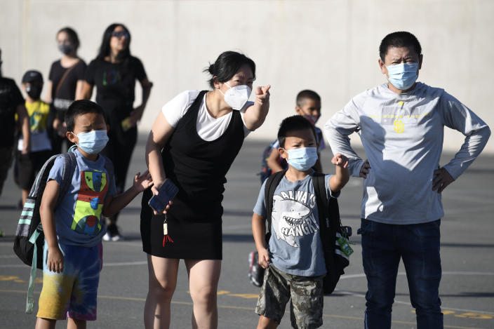 Masked parents direct their children on the first day of school at Enrique S. Camarena Elementary School, Wednesday, July 21, 2021, in Chula Vista, Calif. The school is among the first in the state to start the 2021-22 school year with full-day, in-person learning. (AP Photo/Denis Poroy)