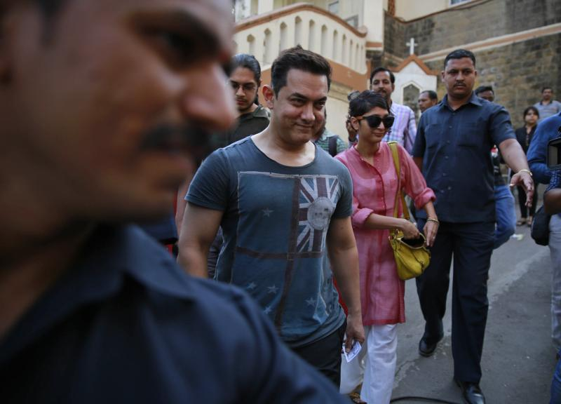 Bollywood actor Aamir Khan, center, arrives with his wife Kiran Rao to cast their vote during the sixth phase of polling of the Indian parliamentary elections in Mumbai, India, Thursday, April 24, 2014.The multiphase voting across the country runs until May 12, with results for the 543-seat lower house of parliament expected on May 16. (AP Photo/Rafiq Maqbool)