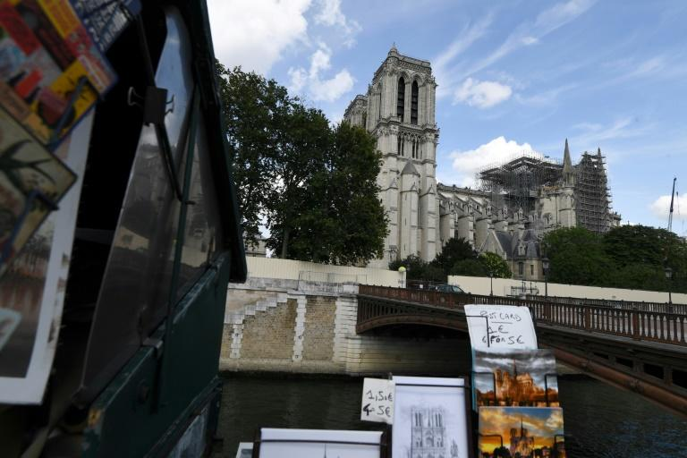 Postcards on sale nearby show Notre-Dame in its pre-blaze glory with the damaged building seen behind following the huge fire three months ago