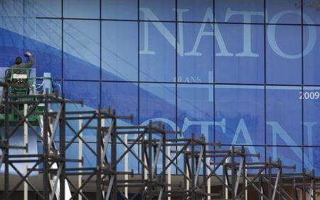 A worker sticks giant logos of the NATO outside Strasbourg's Congress Center