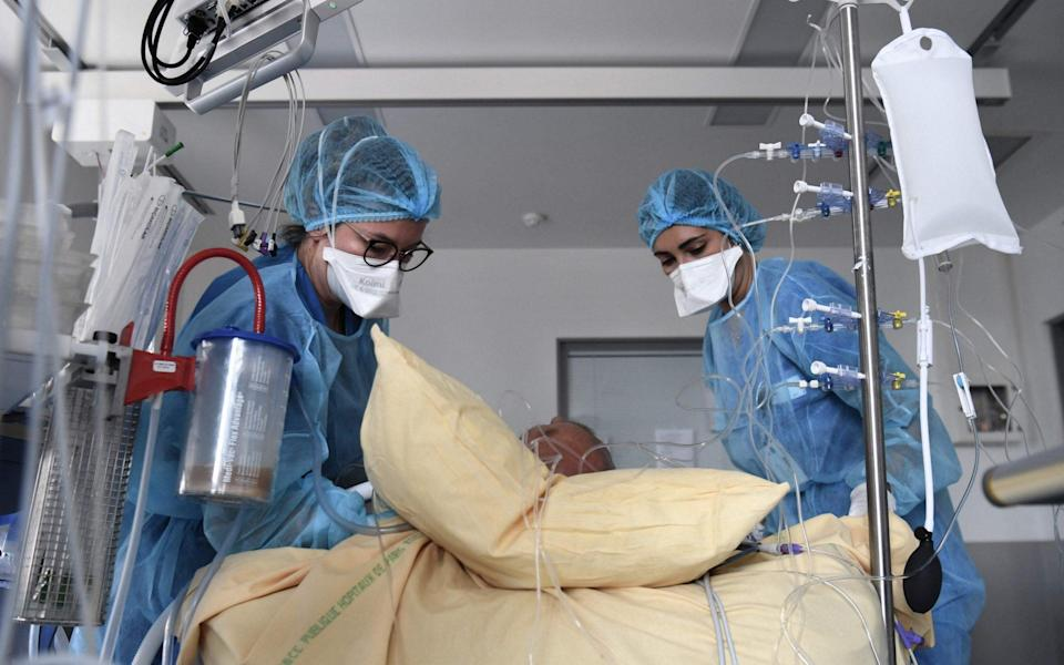 Medical staff members tend to a Covid-19 patient in a room of the intensive care unit of the Henri Mondor Hospital in Creteil, near Paris