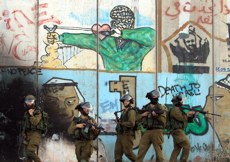 Israeli soldiers stand in front of the graffiti covered controversial separation-barrier during clashes with Palestinian stone throwers at the Israeli Qalandiya checkpoint between the West Back city of Ramallah and Jerusalem, on August 13, 2014 (AFP Photo/Abbas Momani)