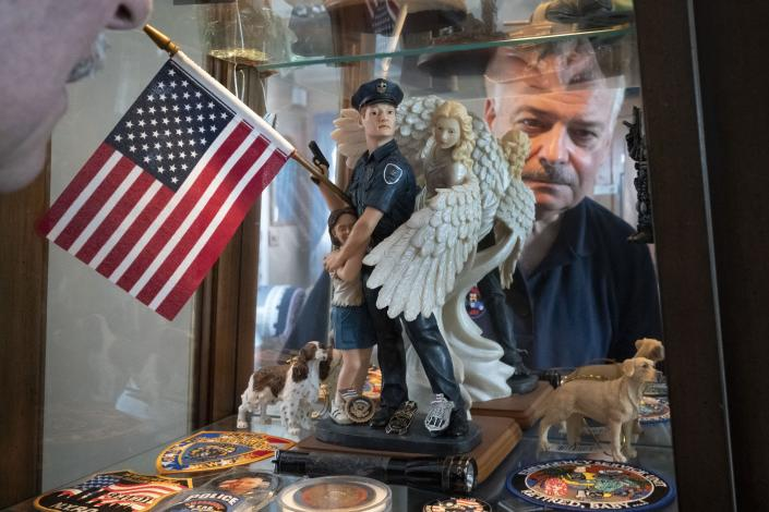 """Retired NYPD Officer Mark DeMarco, is seen in a reflection off a display cabinet where he keeps memorabilia from 9/11 including the small flashlight which he used to help him navigate his way out of the rubble of the fallen skyscrapers, in his home in the Staten Island borough of New York on Tuesday, Aug. 3, 2021. He worries that the public memory of the attacks is fading, that the passage of time has created a false sense of security. """"Have fun with life. Don't be afraid,"""" he says. """"But be mindful."""" (AP Photo/Wong Maye-E)"""