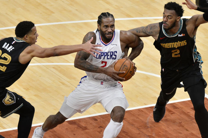 Los Angeles Clippers forward Kawhi Leonard (2) drives between Memphis Grizzlies guard Desmond Bane (22) and center Xavier Tillman (2) during the second half of an NBA basketball game Friday, Feb. 26, 2021, in Memphis, Tenn. (AP Photo/Brandon Dill)
