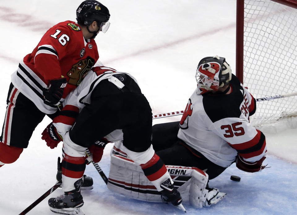 New Jersey Devils goalie Cory Schneider, right, tries to stop a shot by Chicago Blackhawks center Marcus Kruger (16) during the second period of an NHL hockey game Thursday, Feb. 14, 2019, in Chicago. (AP Photo/Nam Y. Huh)