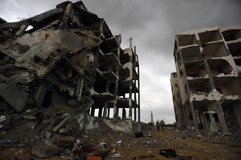 Palestinians walk near the ruins of their house in the northern Gaza Strip town of Beit Lahia on February 19, 2015