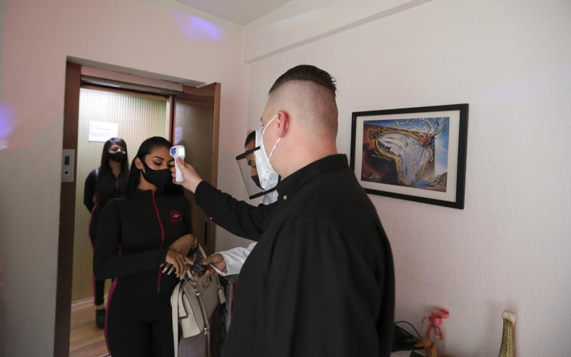 A client wearing a protective face mask measures the temperature of a dancer as she enters his home, in Mexico City, Saturday, Aug. 8, 2020. The pandemic has forced business to adapt to a new normality and the adult entertainment industry is no exception. After three months of inactivity, Mi Ultimo Beso relaunched its table-dance-at-home service observing health measures. (A