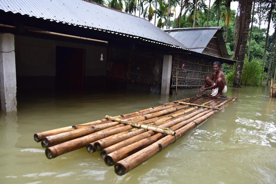 A villager sit on a makeshift bamboo raft near his partially submerged house following flood due to monsoon rain at a village in Nagaon District of Assam. (Photo credit should read Anuwar Ali Hazarika/Barcroft Media via Getty Images)