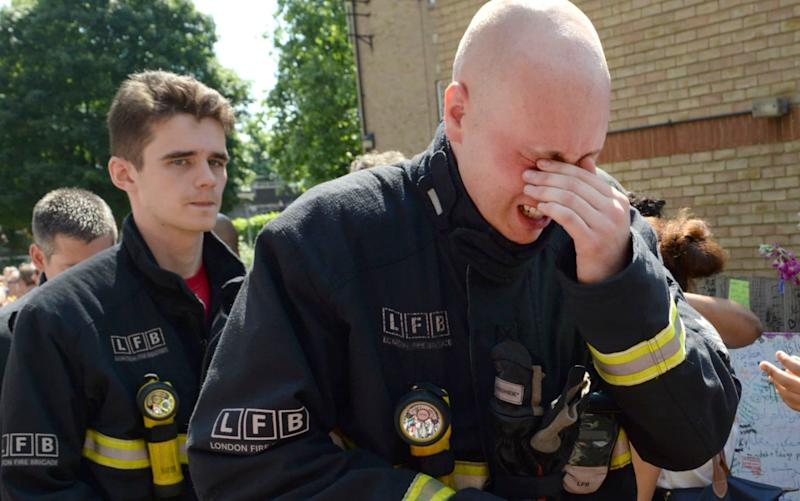 Kensington firefighters attend a minute's silence at the site of the Grenfell Tower blaze - © Eddie Mulholland