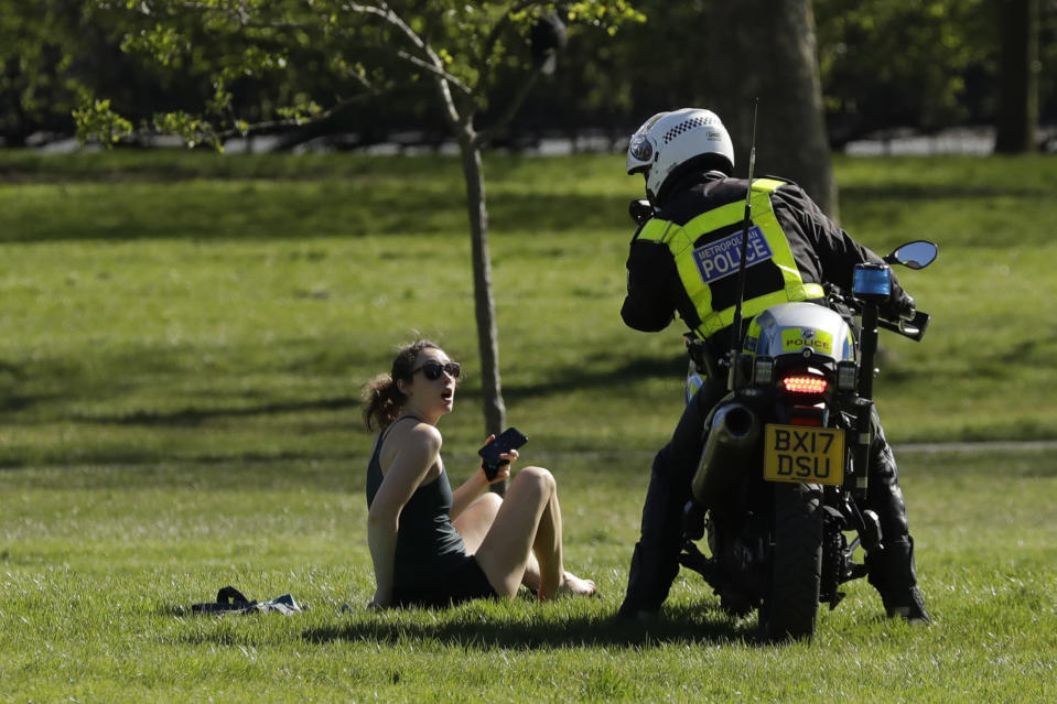 A woman is told to go home by a police officer on a motorbike to stop the spread of coronavirus and keep the park open for people observing the British government's guidance of social distancing, only using parks for dog walking, one form of exercise a day, like a run, walk, or cycle alone or with members of the same household, on Primrose Hill in London, Sunday, April 5, 2020. The new coronavirus causes mild or moderate symptoms for most people, but for some, especially older adults and people with existing health problems, it can cause more severe illness or death. (AP Photo/Matt Dunham)