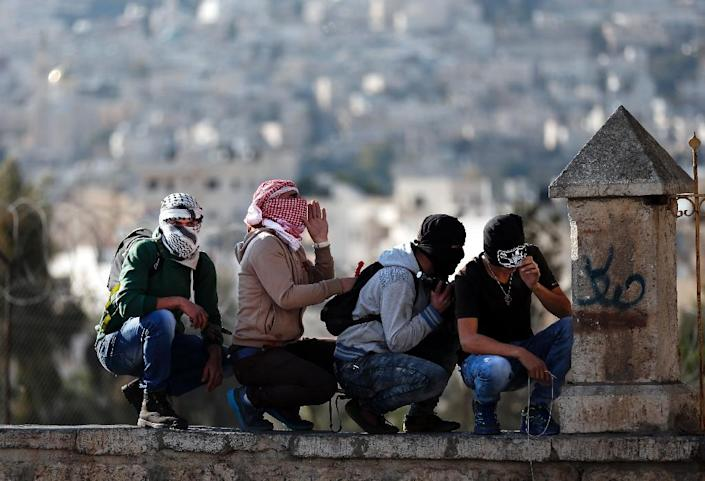 Masked Palestinian stone throwers take cover during clashes with Israeli security forces following a demonstration in the West Bank city of Bethlehem, on December 18, 2015 (AFP Photo/Thomas Coex)