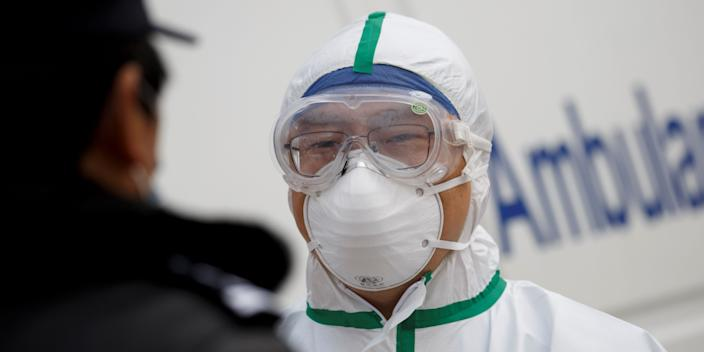 A hospital staff member in protective garments talks to a police officer at a checkpoint to the Hubei province exclusion zone at the Jiujiang Yangtze River Bridge in Jiujiang