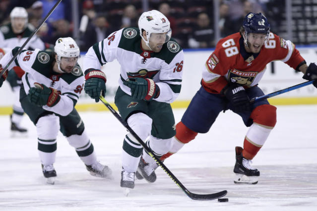 Minnesota Wild left wing Jason Zucker (16) skates with the puck as Florida Panthers center Mike Hoffman (68) defends during the second period of an NHL hockey game, Tuesday, Dec. 3, 2019, in Sunrise, Fla. (AP Photo/Lynne Sladky)