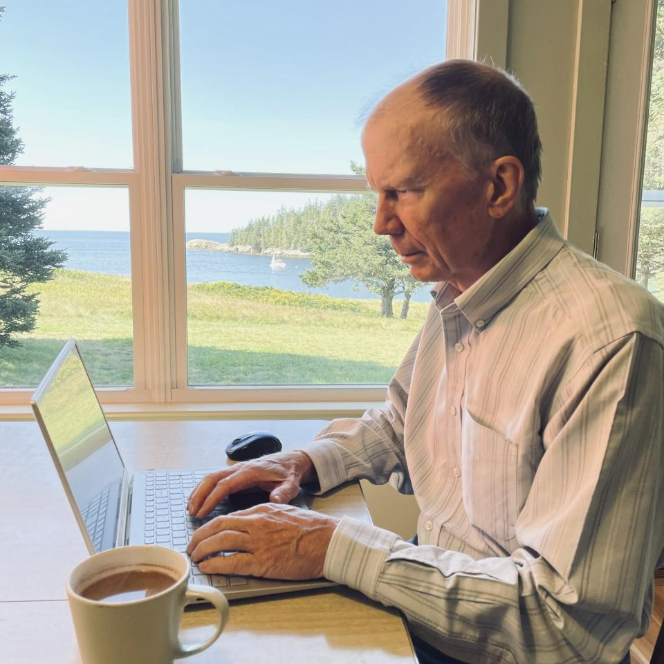 In this photo provided by Donna Hopkins, Charlie Hopkins looks at his laptop computer at his home on Isle au Haut, Maine, on Sept. 4, 2021. Hopkins, who has slow internet speeds, is part of a committee looking for ways to improve internet service on the island. He has concerns about a U.S. Treasury Department rule that narrows the eligibility for broadband infrastructure spending under the American Rescue Plan, which provides $350 billion of flexible funds to state and local governments. (Donna Hopkins via AP)
