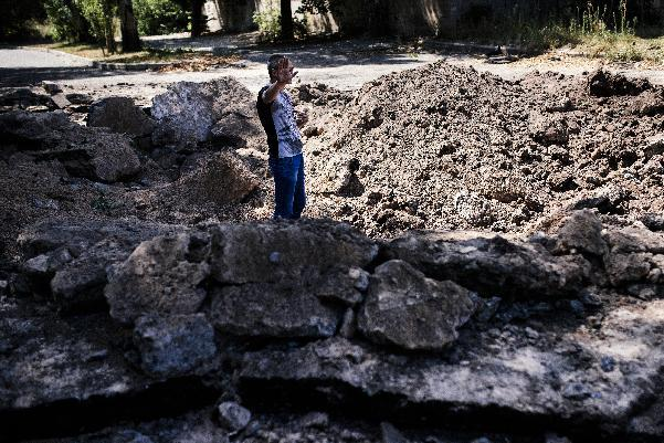 "A man gestures while standing in a bomb crater in а street after an ""air strike"" overnight in Donetsk, on August 6, 2014 (AFP Photo/Dimitar Dilkoff)"