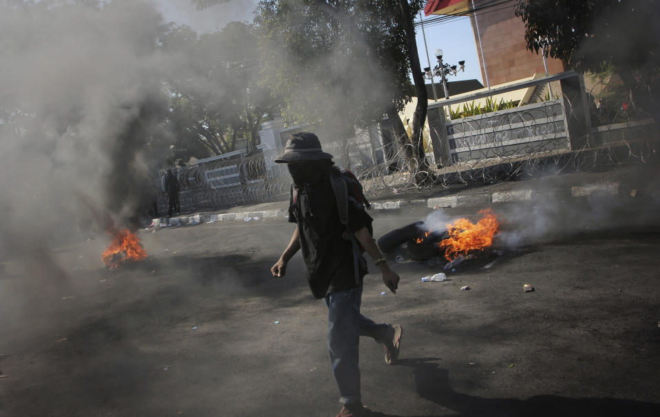A student protester walks past burning tires during a rally in Makassar, South Sulawesi province, Indonesia, Thursday, Sept. 26, 2019. Protests continue in several cities in the country as students rallied against a new law that critics say cripples the country's anti-corruption agency. (AP Photo/Masyudi Syachban Firmansyah)